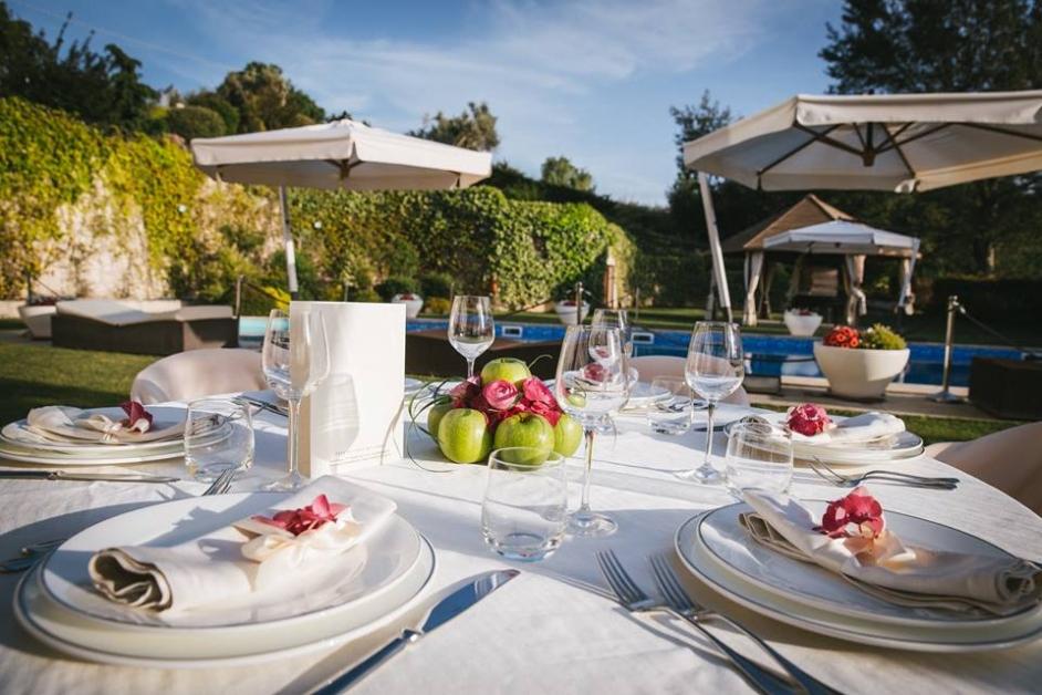 Tavolo apparecchiato all'esterno con vista piscina- Tenuta Villa dei Fiori